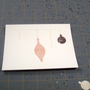 Using tape runner adhesive to apply ornament shapes to holiday card