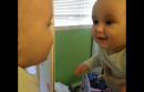 baby kissing himself in the mirror