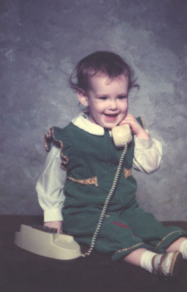 toddler girl smiling and playing with a toy phone