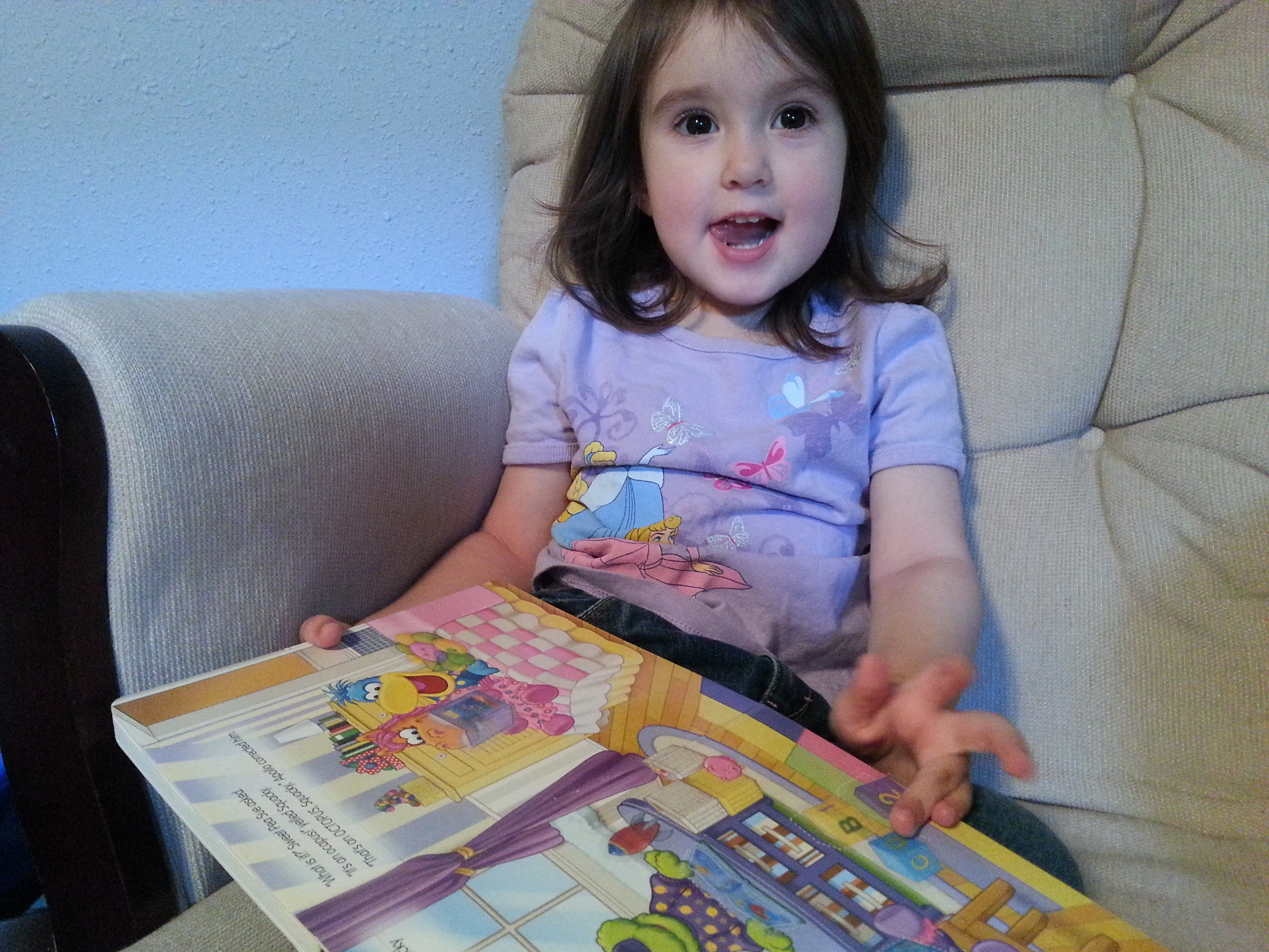 toddler girl sitting in chair with book