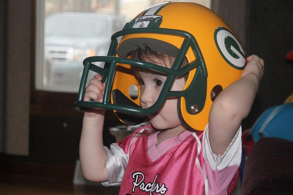 toddler girl wearing Packer helmet and pink jersey