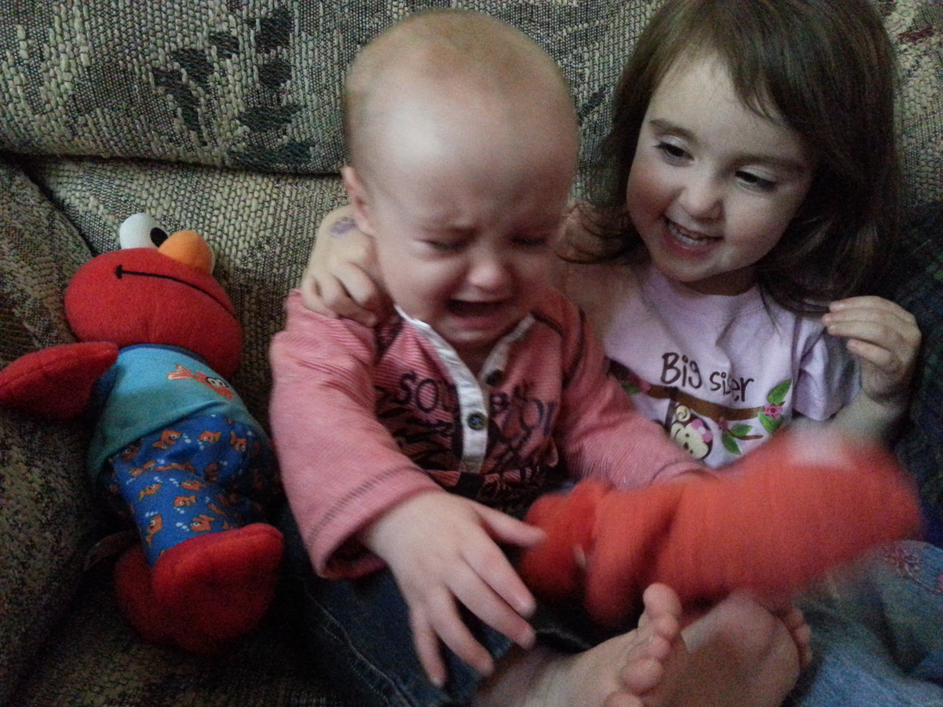 kids sitting on couch one crying