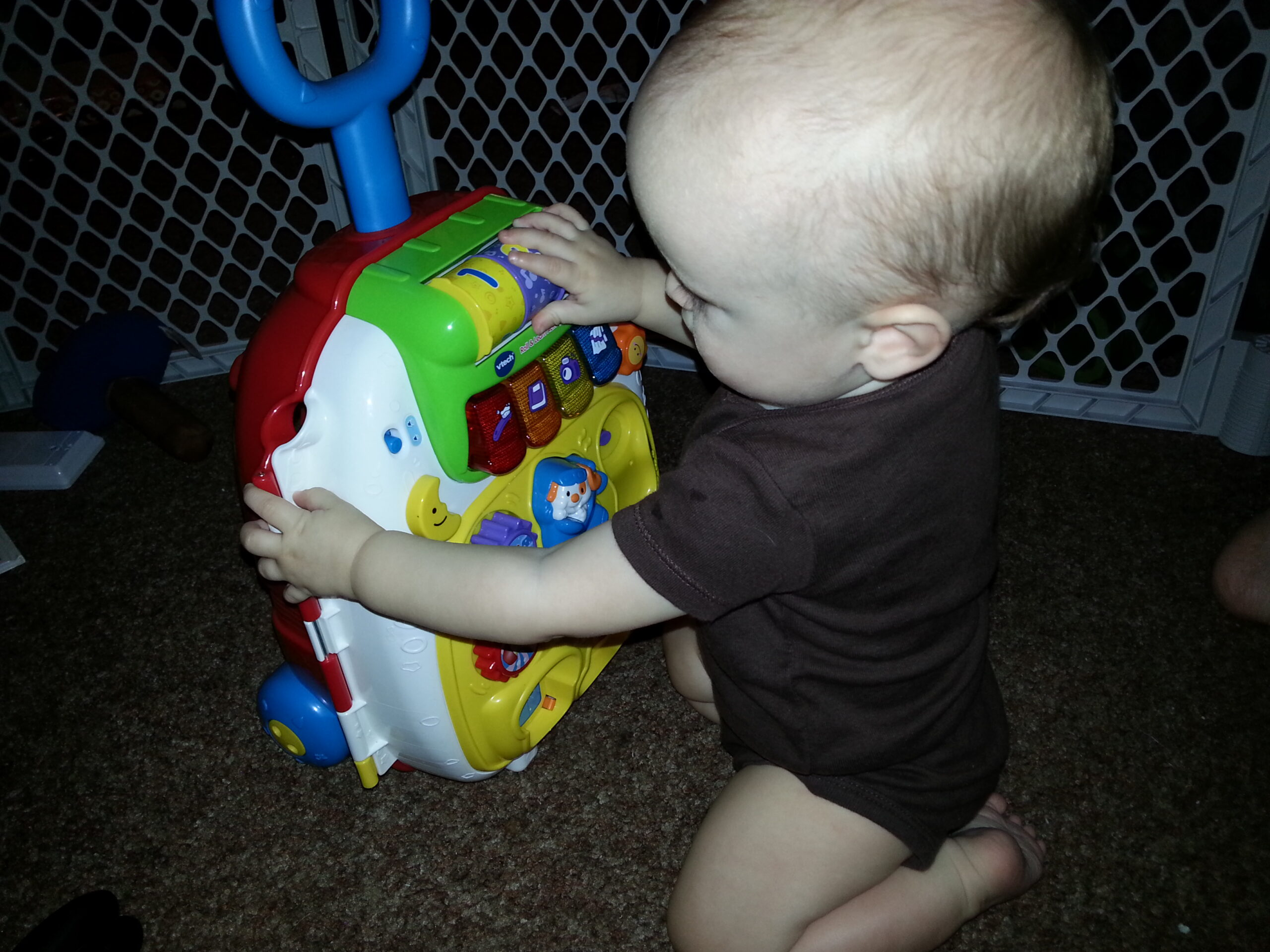 baby playing with vtech roll and learn suitcase