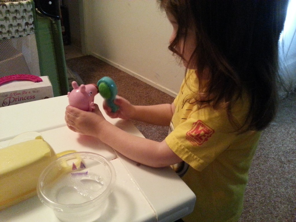 toddler playing with peppa pig toy