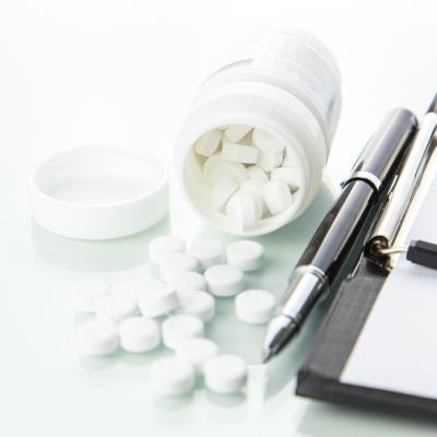 bottle of pills spilled next to prescription pad