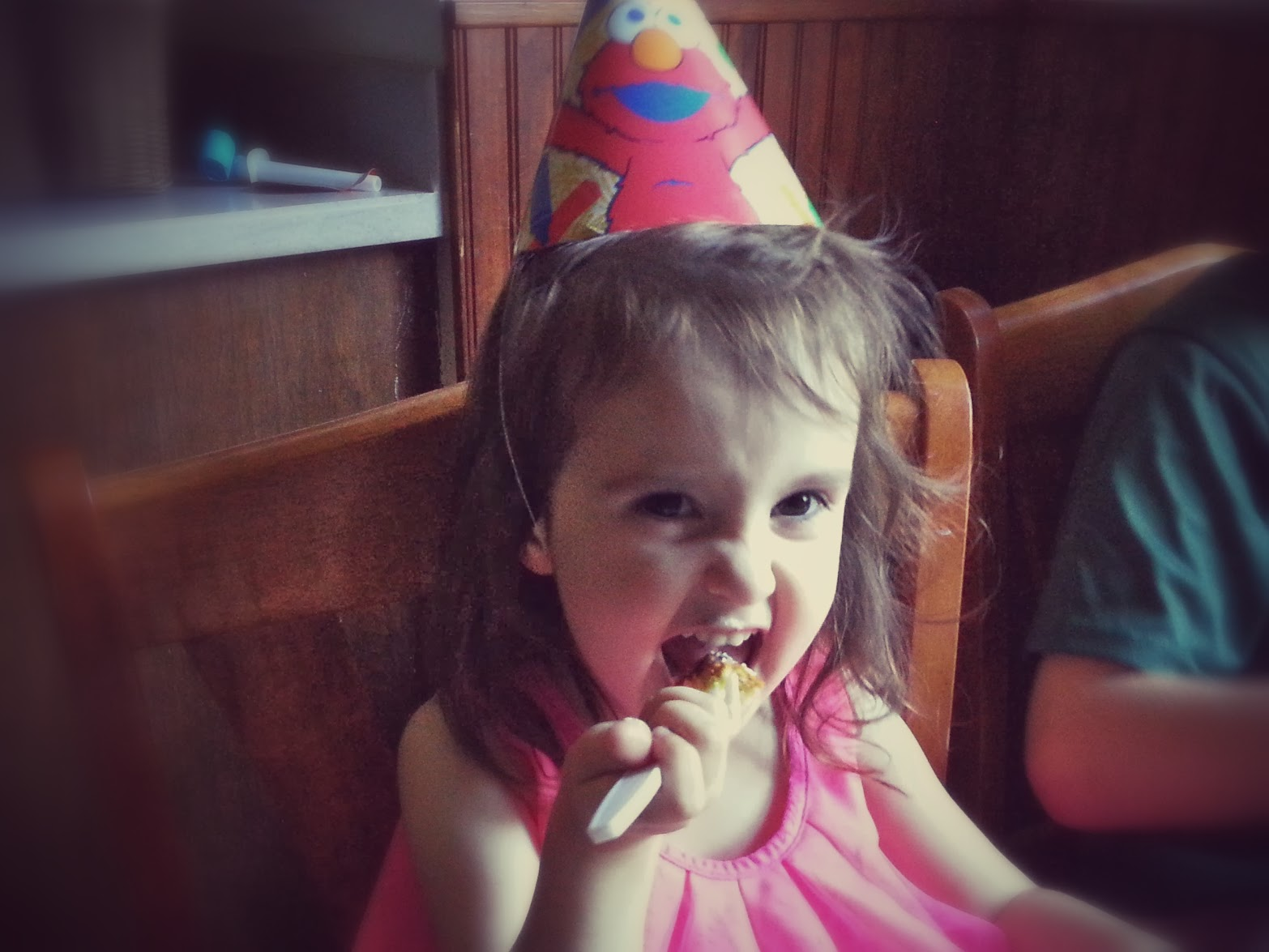 toddler wearing party hat and eating cake