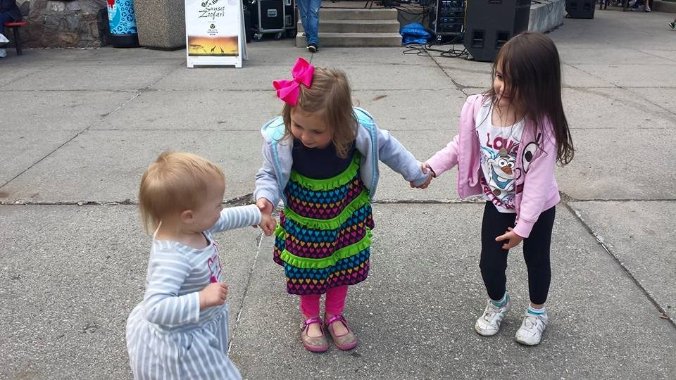 Little girls dancing together outside.