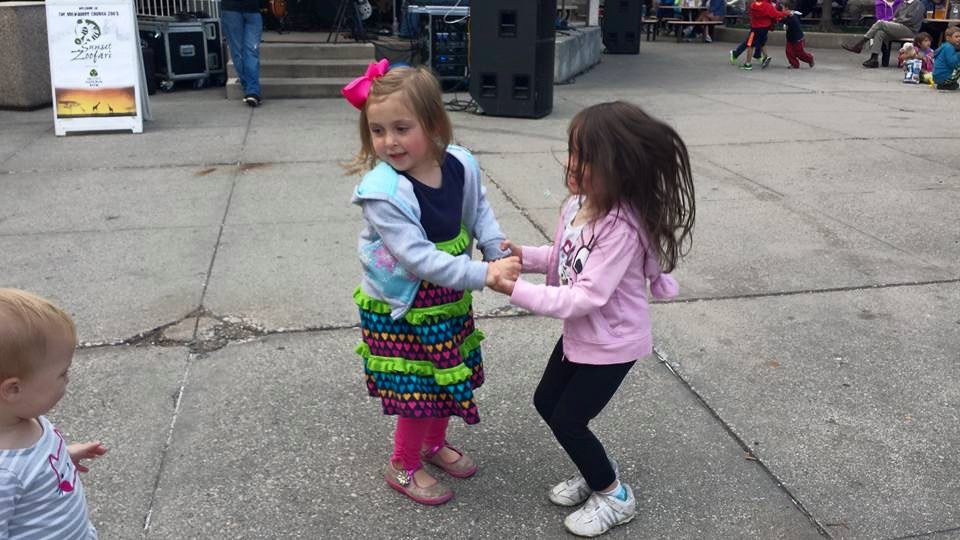 Two little girls dancing together.