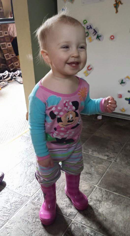 Smiling baby wearing pajamas and boots