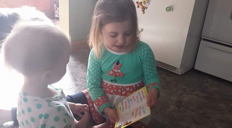 Older sister reading a book to baby sister
