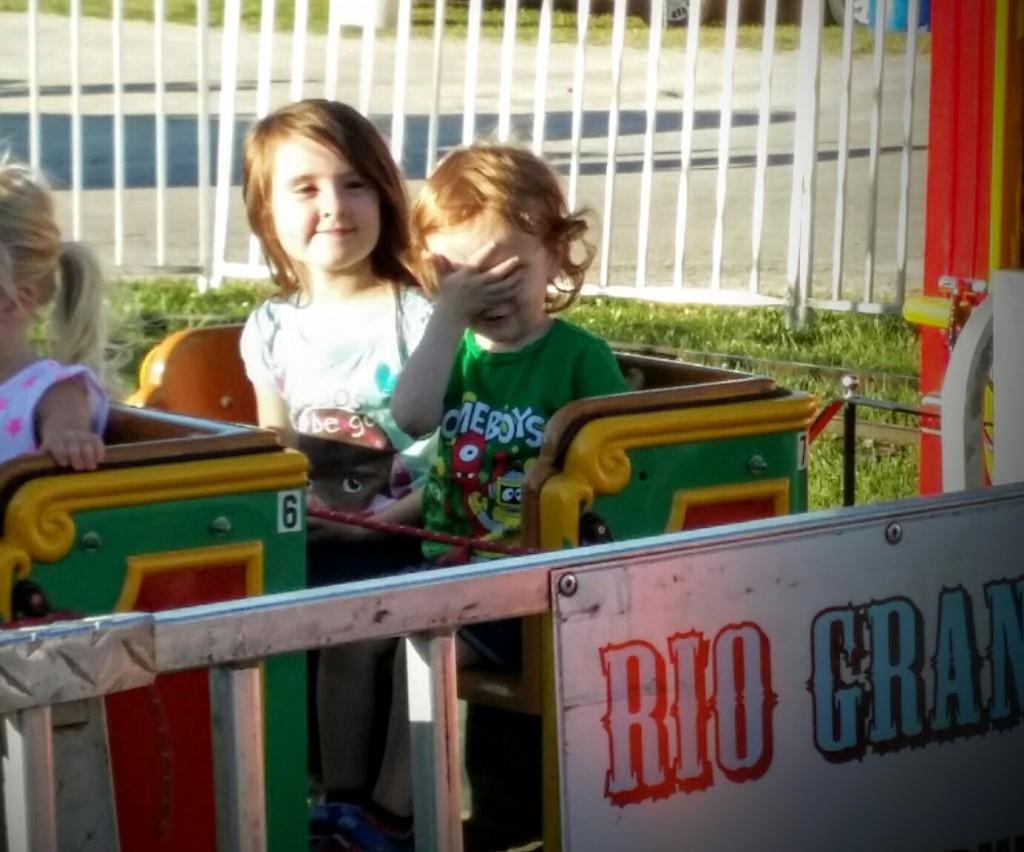 Little boy facepalming on a carnival train ride.