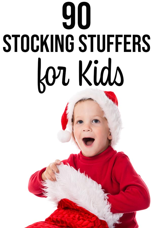 Surprised boy wearing red shirt and Santa hat reaching into a Christmas stocking.