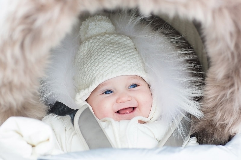 Happy smiling baby wearing a white knit ha and white winter coat in a stroller.