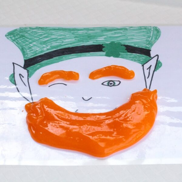 Laminated hand drawn leprechaun face with green hat with orange slime eyebrows and beard.
