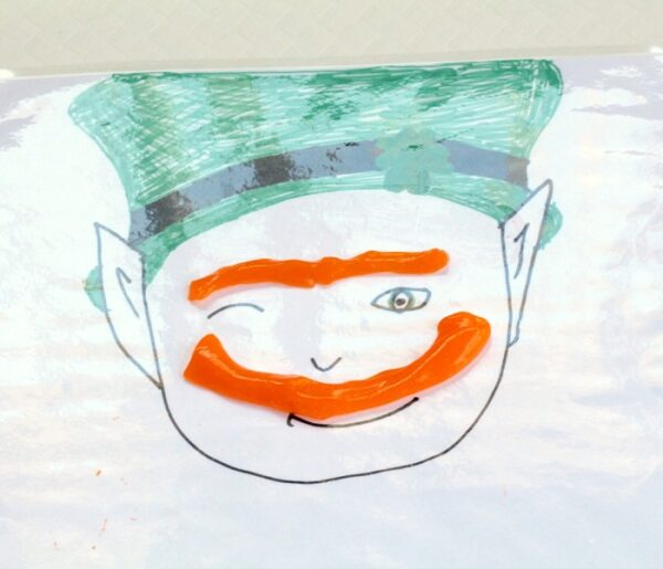 Leprechaun slime sensory play kids activity for St. Patrick's Day using slime to make mustache and eyebrow.
