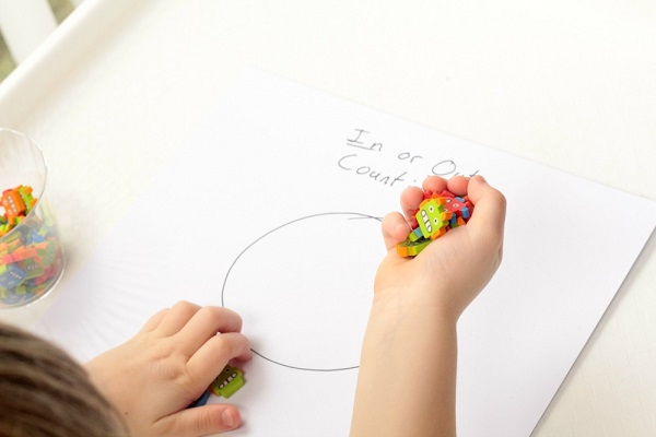 Show your child how to drop the erasers over the counting mat.