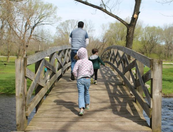 My family walking across a pedestrian bridge at a park.
