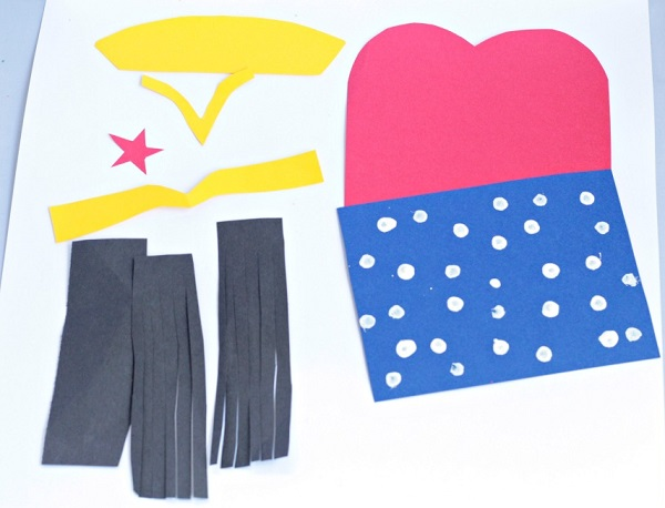 Cut construction paper to make a Wonder Woman paper bag craft.
