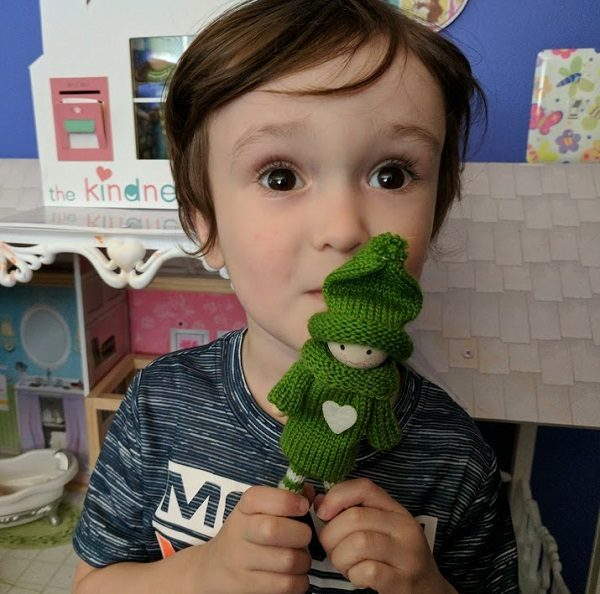My son holding a green Kindness Elf.