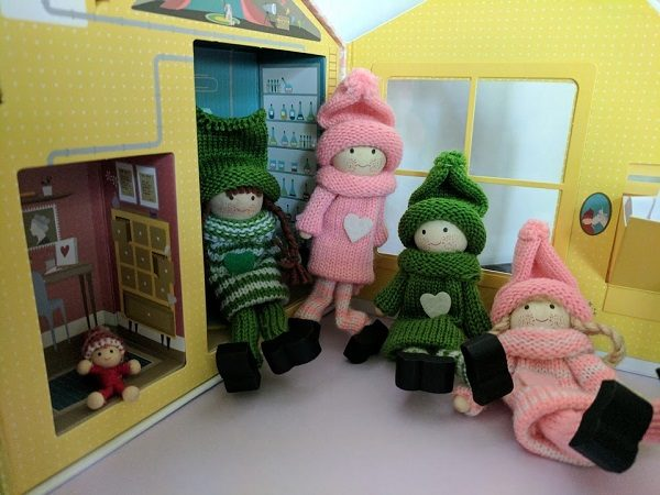Pink and Green Kindness Elves posed by their house.