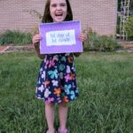 Girl holding first day of first grade printable photo sign