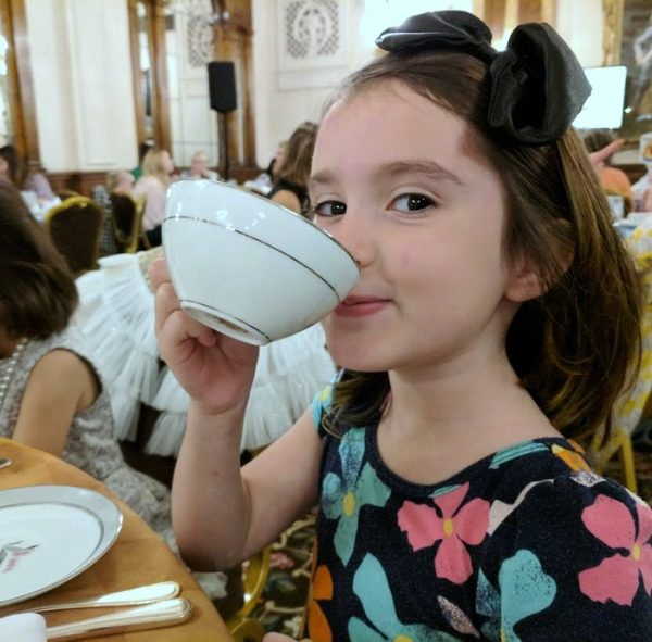 My daughter sipping hot chocolate from a tea cup.