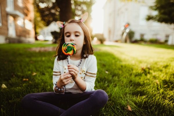 Author's daughter sitting in the grass with a colorful lollipop