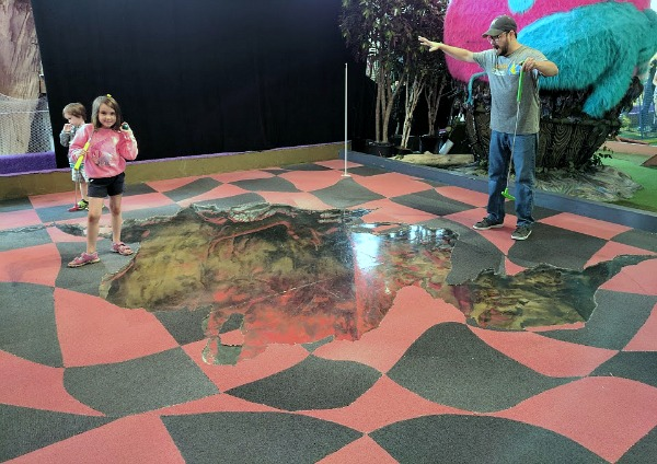 Artist designed mini golf at Can Can Wonderland looks like guests are on ledge of pit.