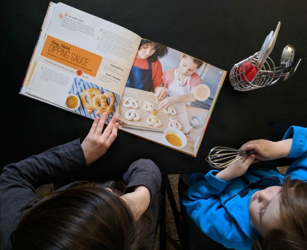 My kids picking out recipes to try from their new cookbook.