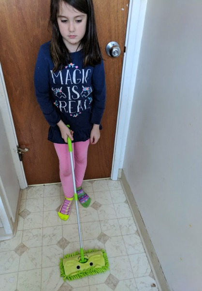 Author's daughter mopping the bathroom floor with kids mop.