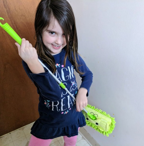 Author's daughter using kids mop as a guitar.