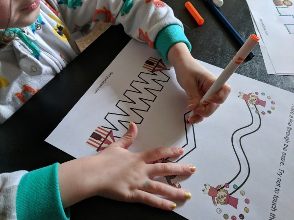 Preschooler practicing early writing skills by tracing lines on circus printable worksheet.