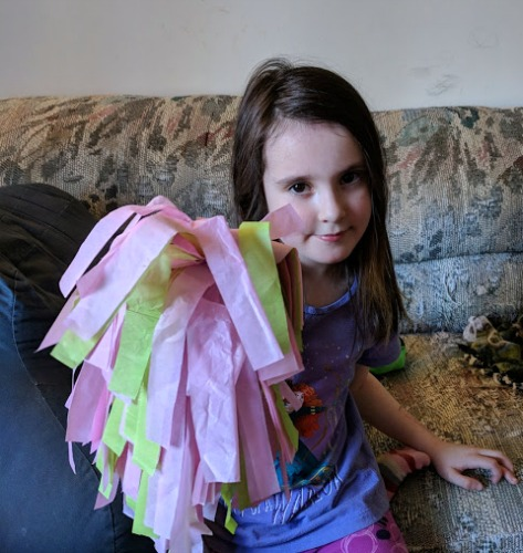 Girl with tissue paper pom pom