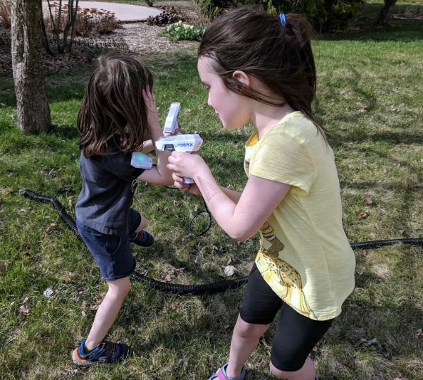 Kids playing outside with Laser X Micro Blaster toys.