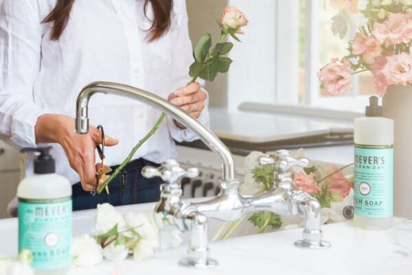 woman trimming flowers at sink