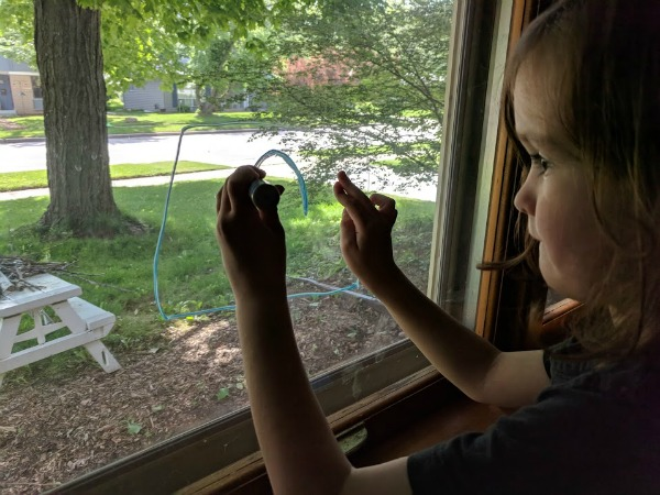 My son drawing on the window with chalk markers