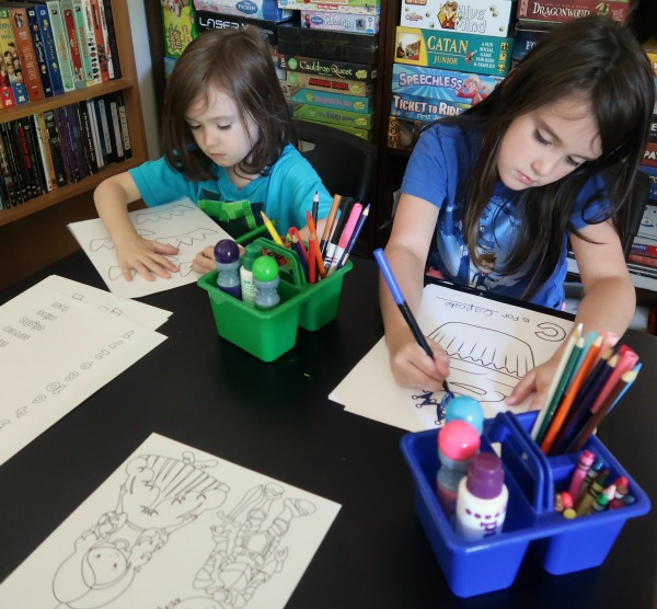 Two kids working on printable fairy tale workbook activity pages.