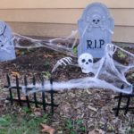 Halloween cemetery decorations outside house.
