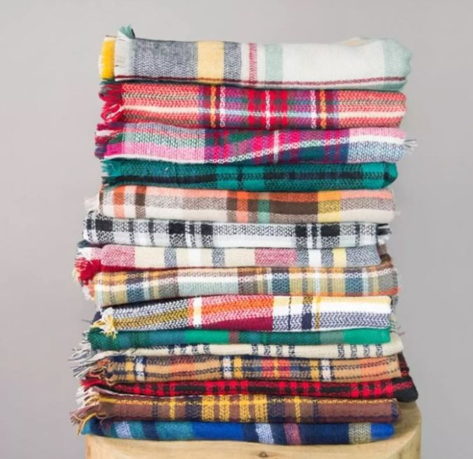 A stack of folded plaid blanket scarves