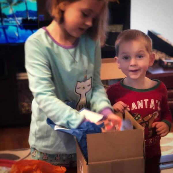 Two kids opening the Stay at Home Gamers Family Game Box.