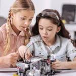 Two girls working on a robot in class