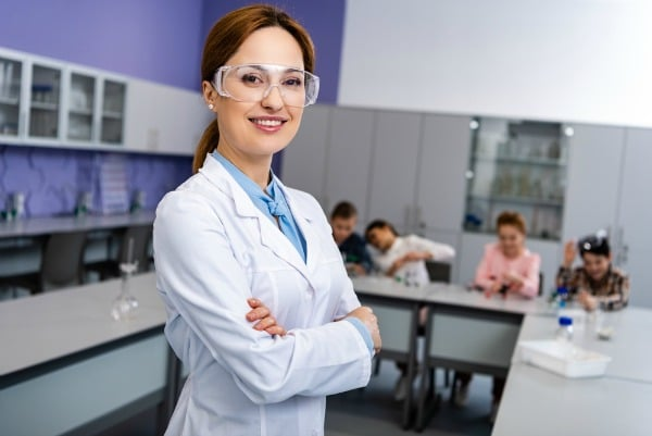 Female scientist wearing lab coat and goggles in classroom science lab setting with students