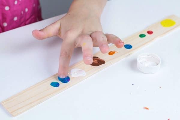Using paint to create fingerprint planets on a paint stir stick.