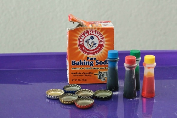 Supplies needed for this fizzy bottle caps science experiment: baking soda, bottlecaps, food coloring