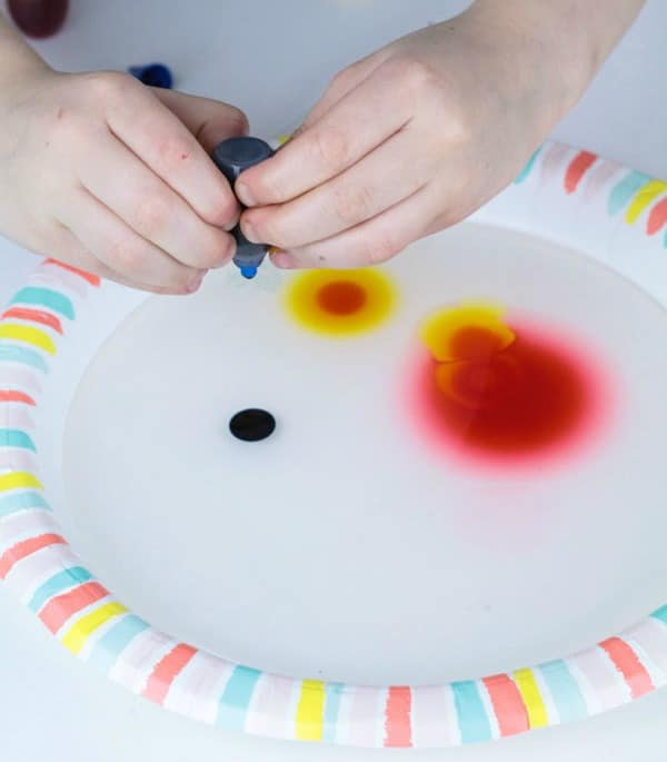 Kid adding food coloring for viscosity activity