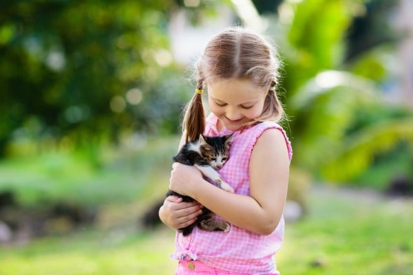 Little girl holding a kitten while outside