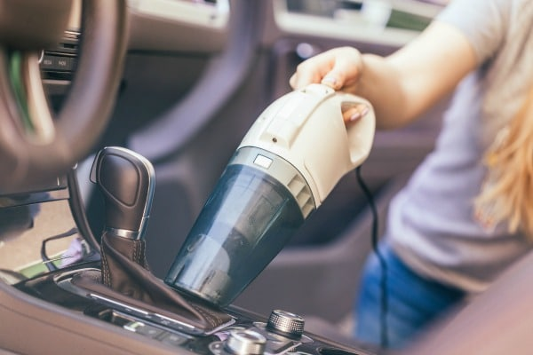 Woman vacuuming the inside of her car.