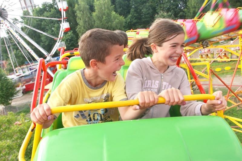 Kids riding roller coaster at an amusement park.