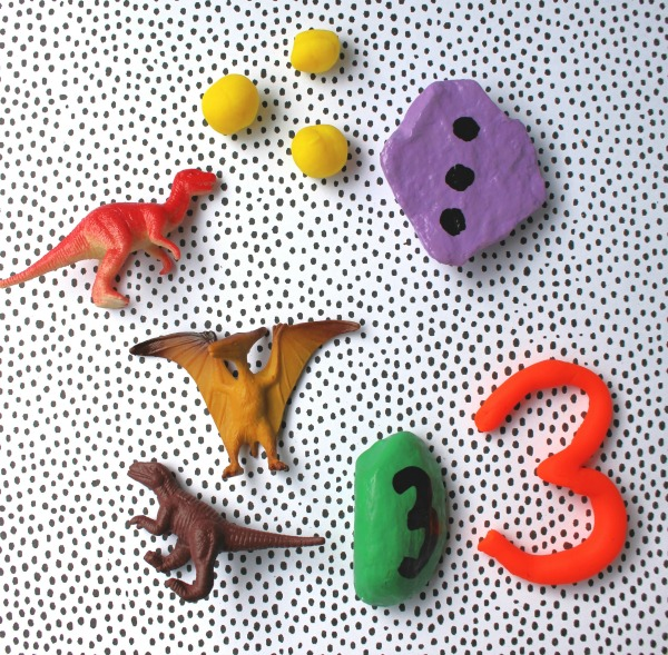 Using playdough and toys with the number 3 rock for a counting activity.