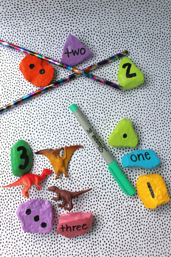 Number rocks with matching amount of pencils, sharpie marker, and dinosaur toys.
